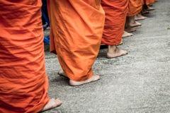 Blootvoets van Boeddhistische monnik terwijl tribune op een rij Stock Afbeeldingen