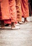 Blootvoets van Boeddhistische monnik terwijl tribune op een rij Stock Afbeelding