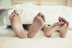 Blootvoets van minnaars onder deken in slaapkamer Vakantie en Happin royalty-vrije stock afbeelding