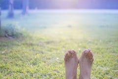 Blootvoets van vrouw het ontspannen op groen gras Stock Foto's