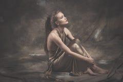 Blootvoetse elegante jonge vrouw in gouden kleding Stock Foto's