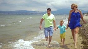 Blootvoetse familie van drie die langs het overzees lopen stock videobeelden