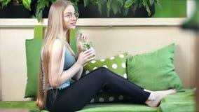 Blootvoetse geschiktheidsvrouw die van de gezonde levensstijl het drinken cocktail van de sapveganist met munt en citroen geniet stock video
