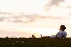 Blootvoetse jonge mens die lettend op de zonsondergang liggen Royalty-vrije Stock Afbeeldingen
