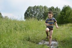 Blootvoetse jongenslooppas door een vulklei Royalty-vrije Stock Afbeeldingen