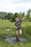 Blootvoetse jongenslooppas door een vulklei Stock Foto's