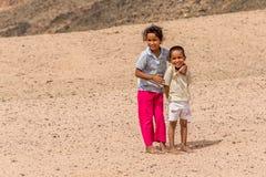 Blootvoetse kinderen in kleren aan flarden in een Bedouin dorp, die voor foto's stellen Royalty-vrije Stock Afbeelding