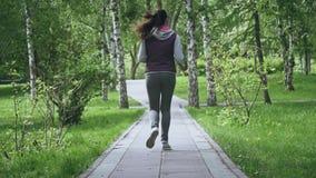 Blootvoetse loopschoenenclose-up Benen van het meisje op een looppas Atleet in tennisschoenen op een looppas in een de zomerpark stock video