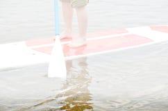 Blootvoetse mens die zich op surfplank met knie-lengte broeken van beschermende kleur bevinden Royalty-vrije Stock Fotografie