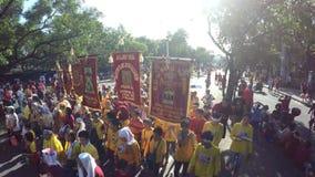 Blootvoetse penitents dragen godsdienstige banners om zich bij Zwarte Nazarene-optocht aan te sluiten stock videobeelden