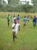 Blootvoetse schoolkinderen die in een spoorgebeurtenis concurreren stock foto