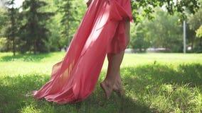 Blootvoetse sexy benen mooie jonge meisjes op de grasclose-up het meisje in de rode kledingsgangen blootvoets op het gras stock video