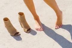 Blootvoetse vrouw naast schoenen Stock Foto