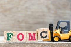 Bloque c de la letra del control de la carretilla elevadora del juguete en comité federal del mercado libre de la palabra FOMC so imagen de archivo libre de regalías