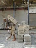 Bloque de cemento que lleva del trabajador de construcción Imagen de archivo