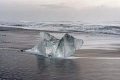 Bloque de hielo en la playa negra imágenes de archivo libres de regalías