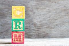Bloque de la letra del color en la gestión de la relación del cliente de la palabra CRM en el fondo de madera imagen de archivo