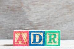 Bloque de la letra del color en la reacción de droga adversa de la palabra ADR en el fondo de madera foto de archivo