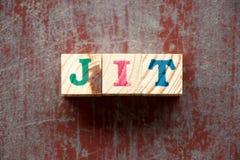 Bloque de la letra en la palabra JIT Abbreviation de apenas a tiempo en fondo de madera rojo stock de ilustración