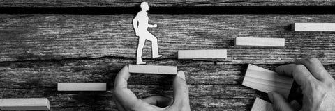 Bloque de la tenencia del hombre como recortes caminan los pequeños de una silueta de una persona imagen de archivo libre de regalías