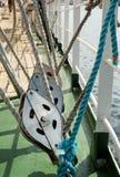 Bloque y cuerdas metálicos de polea en la cubierta de un velero Fotos de archivo libres de regalías