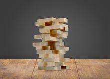 Bloquea el jenga de madera del juego en el fondo de madera del negro del piso Foto de archivo libre de regalías