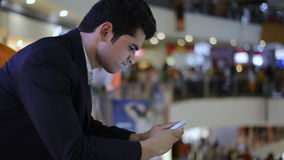Bloqueado-en tiro de un hombre de negocios usando un teléfono móvil en alameda de compras almacen de video