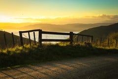 Bloquee la entrada a la pista que camina al lado del camino rural metalled con la cerca del bastón y de alambre, península de Mah imagenes de archivo