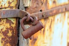 Bloqueo aherrumbrado en puerta resistida Foto de archivo libre de regalías