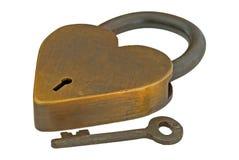 Bloqueo auténtico y clave del corazón de cobre amarillo aislados Imagen de archivo
