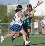 Bloqueo del defensor del lacrosse de las muchachas Imagen de archivo libre de regalías