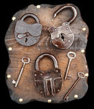 Bloqueos viejos y claves en tablón de madera Imagen de archivo libre de regalías