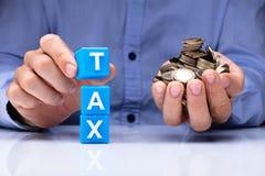 Bloques c?bicos del impuesto de la tenencia de la persona y monedas de oro fotos de archivo