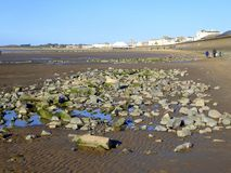 Bloques de cemento en la playa de la arena fotos de archivo