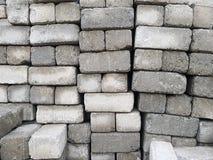 Bloques de cemento llenados encima de uno a - pilas de ladrillos del cemento fotografía de archivo