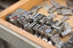 Bloques de impresión de la prensa de copiar de la ventaja del vintage contra un fondo de madera resistido del cajón con el bokeh Fotografía de archivo