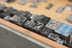 Bloques de impresión de la prensa de copiar de la ventaja del vintage contra un fondo de madera resistido del cajón con el bokeh Foto de archivo libre de regalías