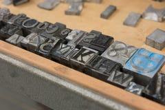 Bloques de impresión de la prensa de copiar de la ventaja del vintage contra un fondo de madera resistido del cajón con el bokeh Imágenes de archivo libres de regalías