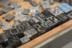 Bloques de impresión de la prensa de copiar de la ventaja del vintage contra un fondo de madera resistido del cajón con el bokeh Fotos de archivo libres de regalías
