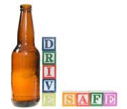Bloques de la letra que deletrean la caja fuerte de la impulsión con una botella de cerveza Imagenes de archivo
