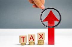 Bloques de madera con las monedas y el impuesto de la palabra y una flecha ascendente El concepto de crecimiento del impuesto en  imagen de archivo libre de regalías