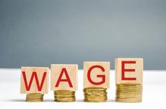 Bloques de madera con las monedas y el salario de la palabra Aumento del sueldo Tarifas salariales Crecimiento de la carrera bene foto de archivo