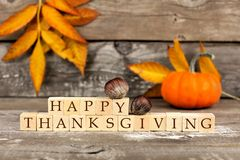 Bloques de madera de la acción de gracias feliz contra la madera rústica con las hojas de otoño Fotos de archivo
