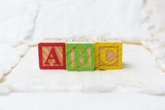 Bloques de madera del alfabeto en el edredón ABC de deletreo horizontal Imagenes de archivo