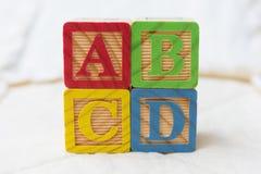 Bloques de madera del alfabeto en el edredón ABCD de deletreo apilados Imagenes de archivo