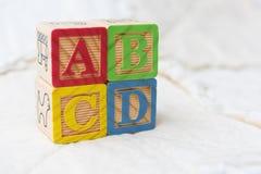 Bloques de madera del alfabeto en el edredón ABCD de deletreo apilados en ángulo Imagen de archivo libre de regalías