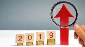 Bloques de madera 2019 y flecha roja para arriba Negocio acertado y confiable Buena perspectiva Dinero de ahorro y planificación  foto de archivo libre de regalías