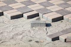 Bloques de pavimentación grises - vista lateral Nueva acera con las piedras rectangulares en el lastre arenoso que pavimenta las  foto de archivo libre de regalías