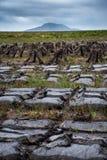 Bloques de sequedad de la turba en el campo en la isla de Uist del norte, con la colina de Eaval en el fondo fotos de archivo libres de regalías