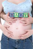 Bloques del alfabeto celebrados contando con a padres sobre el vientre de la mama Foto de archivo libre de regalías